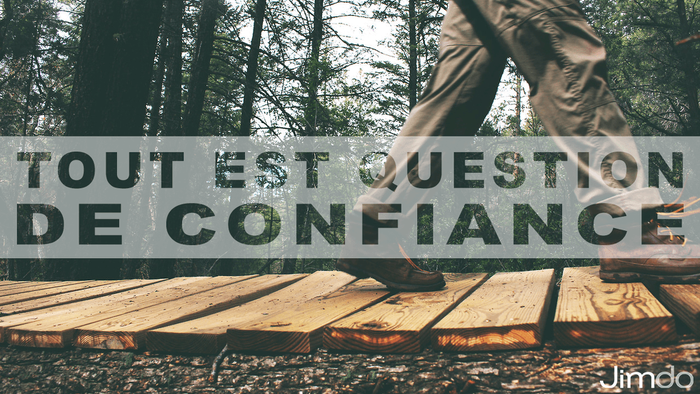 """Homme marchant sur un sentier en forêt, incrustration du texte """"Tout est question de confiance"""" sur l'image"""