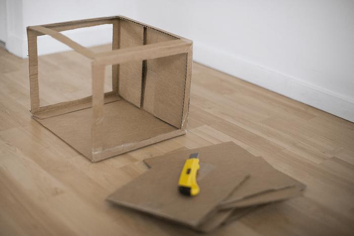 Carton avec 3 côtés découpés et cutter posé sur des bouts de carton