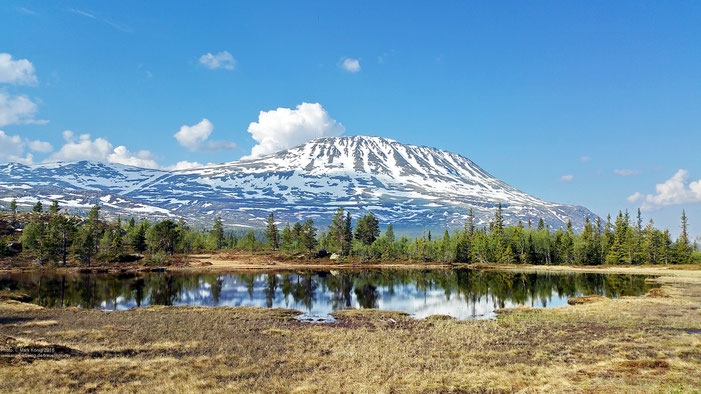 Photo of snow-capped mountain Gaustatoppen with blue sky, a partly mirrorig lake in the foreground