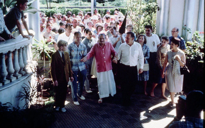 1962 : East-West Gathering - Charles Haynes in brown jacket left of Meher Baba, Lud Dimpfl assisting, Anita De Caro-Vieillard on the far right, Henry Kashouty behind Baba and Meherwan Jessawala holding umbrella ; Photo courtesy of Charles Haynes