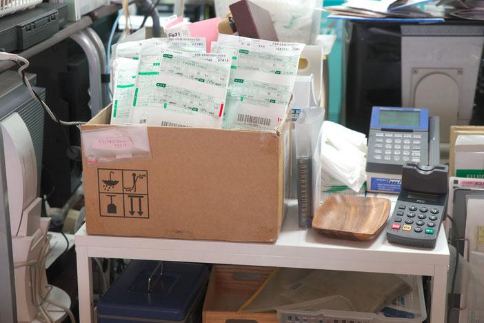 ダンボール箱に現像済のフィルムとプリントの入った袋がいくつか入れられている