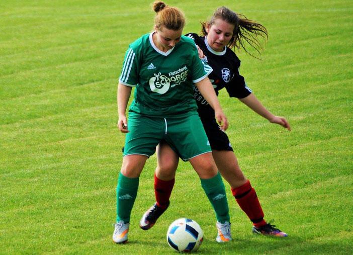 Eine Spielerin von Kickers Erdhausen schirmt den Ball gegen die FSG-Angreiferin Sarah Braun (re.) ab