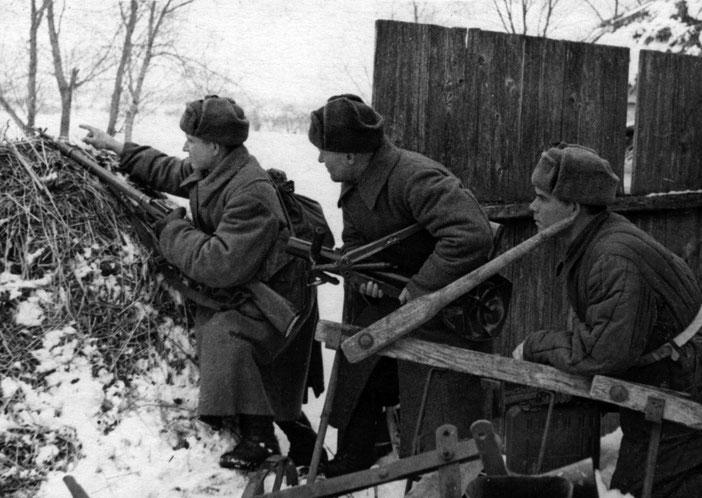 Красноармейцы скрытно выдвигаются на боевую позицию в деревне во время битвы под Москвой. У бойца в центре в руках ротный 50-мм миномет