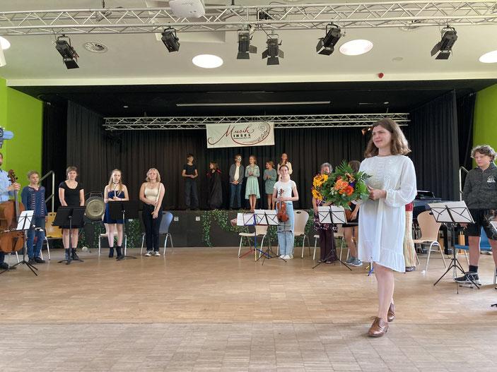 """Auf einer mit Blumen geschmückten Bühne stehen ein Kinderchor und sitzen Instrumentalisten der Musikinsel Finkenwerder beim Abschlusslied der """"Däumelinchen""""-Aufführung."""