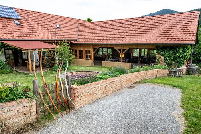 Links die Werkstatt mit zusätzlichen Outdoor-Arbeitsplätzen, rechts die riesige Terrasse fürs Bogenschießen
