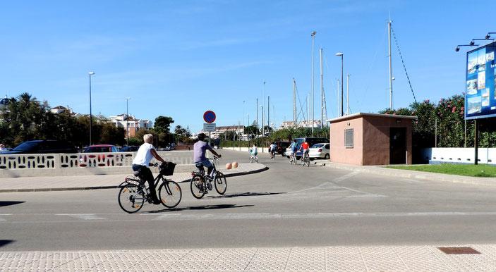 Un grupo de ciclistas pasea por delante del Marino Rotes, junto a la Marina de Dénia y la playa