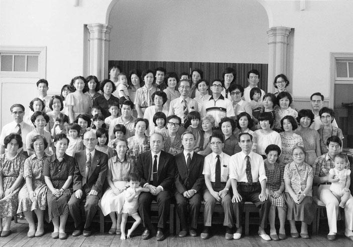 脇本寿牧師(1959年~1991年)の就任20周年感謝礼拝の記念写真。中央左寄りのこどもさんをはさんで、脇本寿牧師とお連れ合いの脇本豊子姉。