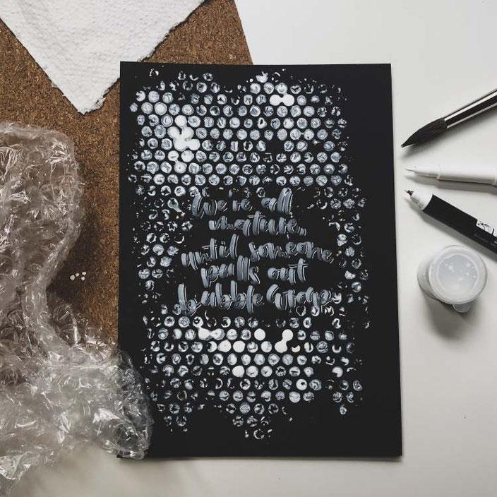 Handlettering in weiss auf schwarz mit einem Hintergrund aus Noppenfolie: We're all mature, until someone pulls out bubble wrap