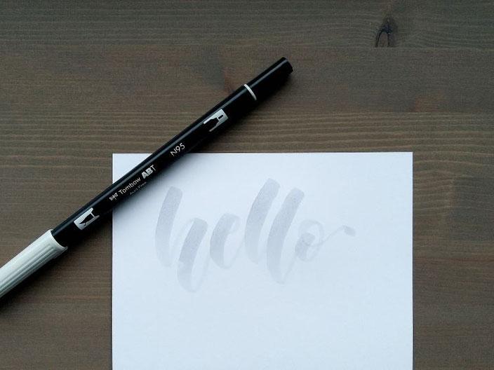 Lettering Anleitung für ein Punkte Lettering - Schritt 1: hello in einer hellgrauen Schrift aufschreiben
