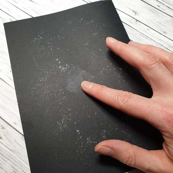 Kreidekrümel auf dem Papier verwischen für ein Kreidelettering auf Papier
