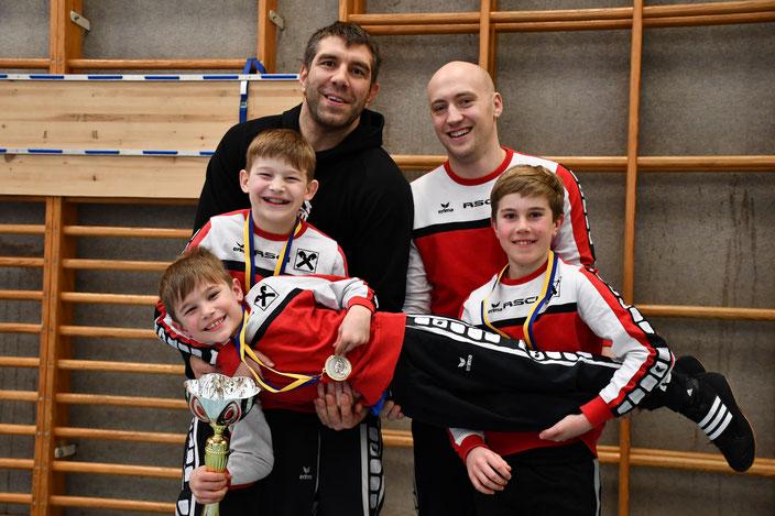 Die drei Turniersieger Noah, Jakob (liegend) und Alois mit ihren Trainern