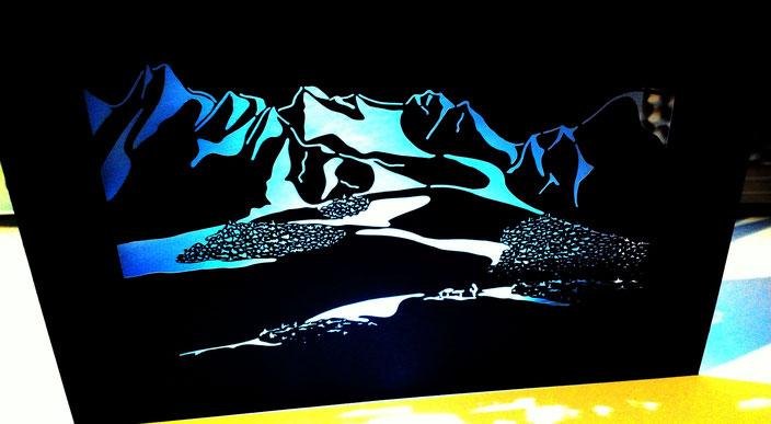 Laserschnitt in schwarzem Karton mit Lichteffekt im Hintergrund