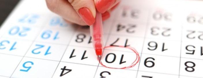 Frau kreist einen Termin auf einem Terminkalender ein.