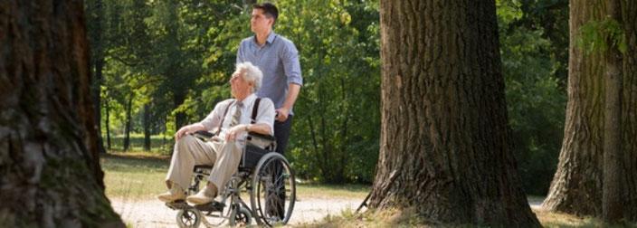 Senior (im Rollstuhl) und Senioren-Assistent machen einen Spaziergang.