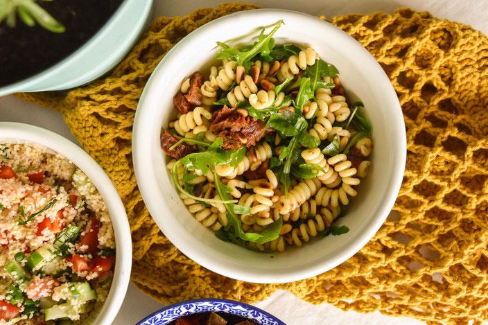 Veganer Nudelsalat mit getrockneten Tomaten, Rucola und Pinienkernen. Foto: RiekesBlog.
