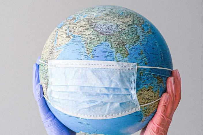 Von zwei Händen hochgehaltener Globus mit medizinischer Maske darüber