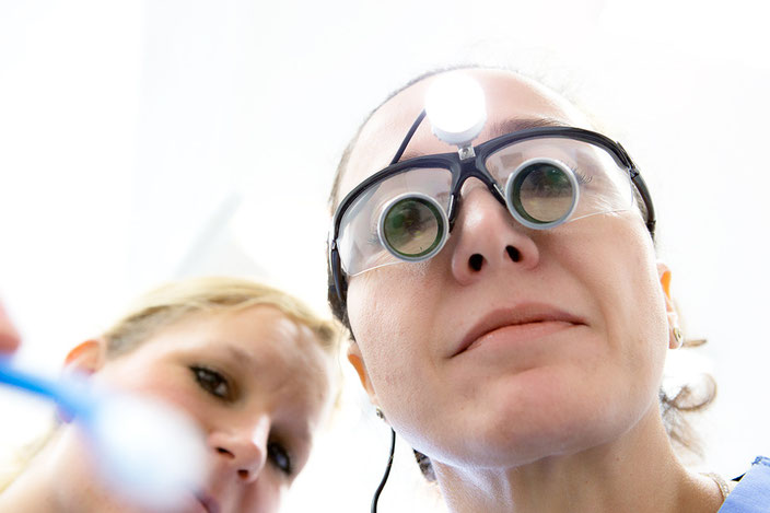 Foto einer behandelnden Zahnärztin aus Patientensicht aufgenommen.