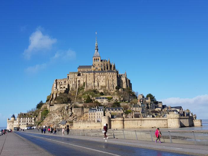 Le Mont Saint-Michel entouré de la baie, accessible via une passerelle
