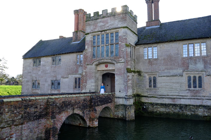 Ich stehe auf der Brücke des Anwesens im Haupttor in einem langen weißen Kleid und Biedermeier-Spencer. This image shows Baddesley Clinton, a historic home, with a bridge on which I stand in a white Regency Dress and blue Spencer