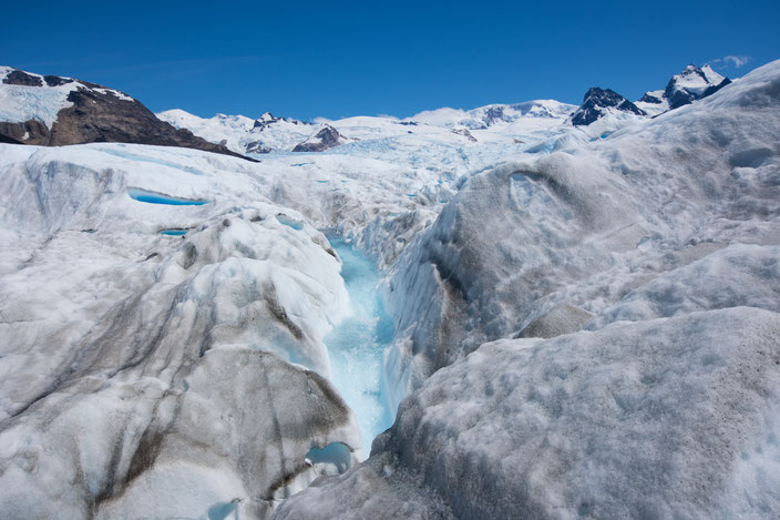 """Das Schmelzwasser formt kleine """"Flüsse"""" in den Gletscher. Manchmal bildet sich sogar ein kleiner Wasserfall."""