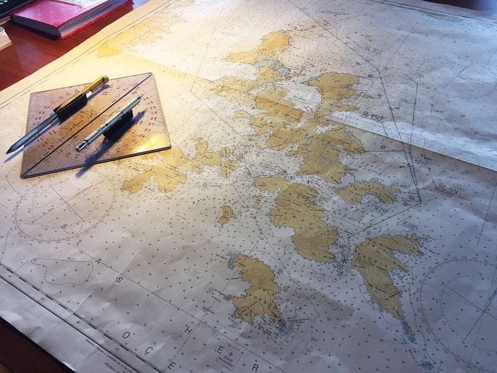 Der Kapitän und seine Crew navigieren mit Karte durch die Fjorde des Feuerlandes.