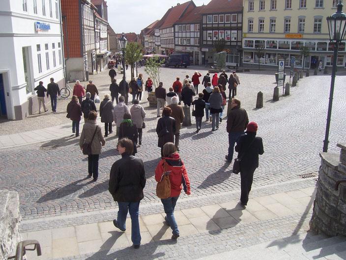 Eine Besuchergruppe bewegt sich in Richtung Marktplatz zum Geschichtsbrunnen.