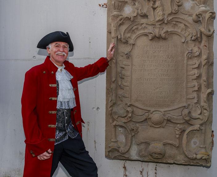Vogt Essich vor seinem Grabstein auf dem Alten Friedhof