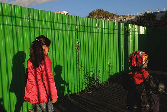 Mathieu Guillochon photographe, Street Photo, photographie, France, enfants, soir, couleurs, rouge, vert, automne, sortie de l'école, ombres, lumière, banlieue, Puteaux, fille, garçon, vélo, casque.