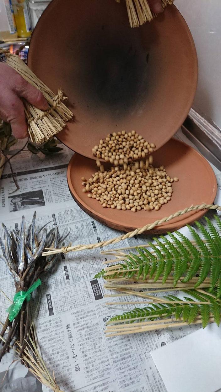 火にかけたほうろくから熱していないほうろくに豆を移す
