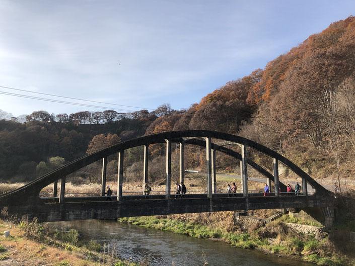 11月18日、湯川橋を渡る御代田フットパスのコース開きイベント参加者の皆さん。