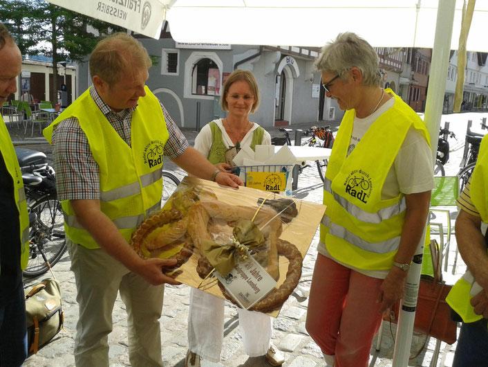 Die Bürgermeister Brenner und Dr. Vonderheid überreichen der RadL-Sprecherin Örmy Meurer in Anwesenheit von Frau Gerhard (Büro für bürgerschaftliches Engagement) eine Geburtstagsbrezel von der Bäckerei Zachert.