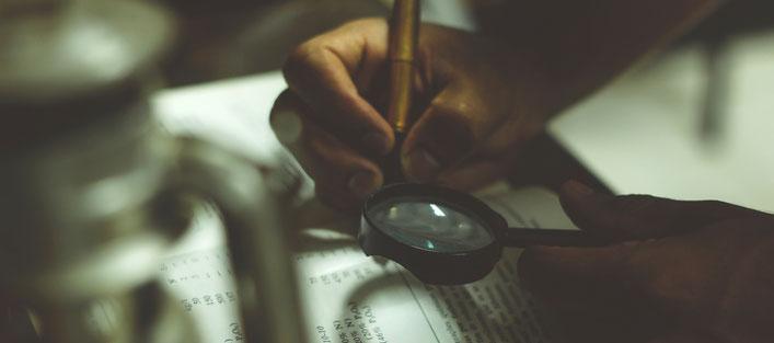 Lupe über einem Buch mit schreibenden Händen