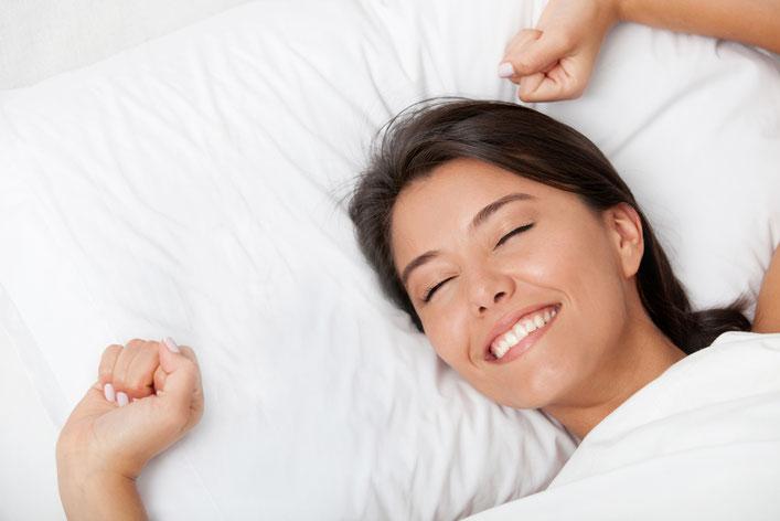 Junge Frau liegt am Rücken in weisser Bettwäsche und hat ein glückliches Lächeln im Gesicht