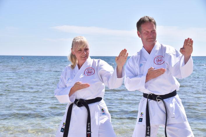 Trainerpaar Friederike Zeifang und Carsten Zeifang vom Shotokan Karate Stade e. V. fröhlich in Kampfhaltung vor Meeresbrandung