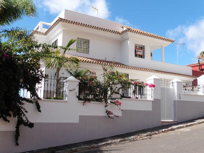 Straßenfrontansicht vom Eingangsbereich mit heller Mauer und dahinter sieht man das 2  geschossige Haus was auch mit weißer Farbe gestrichen ist.