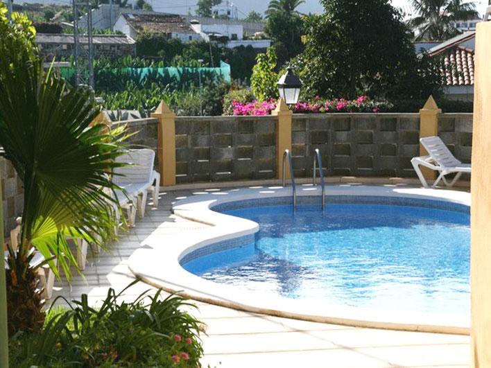 Gemeinschaftspool mit Liegen zum Sonnen und der Pool ist in Form einer Acht gebaut.