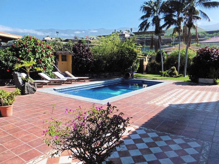 Pool der Villa mit großer gefliester Terrasse, und mit Pflanzen eingefasst sowie Blick in die Berge im Hintergrund.