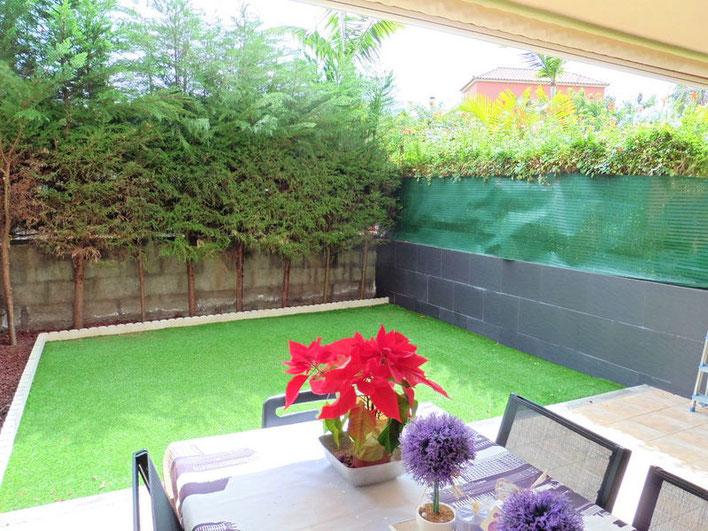 Terrasse und keliener Garten der mit einer undurchsichtigen Hecke umgeben ist.