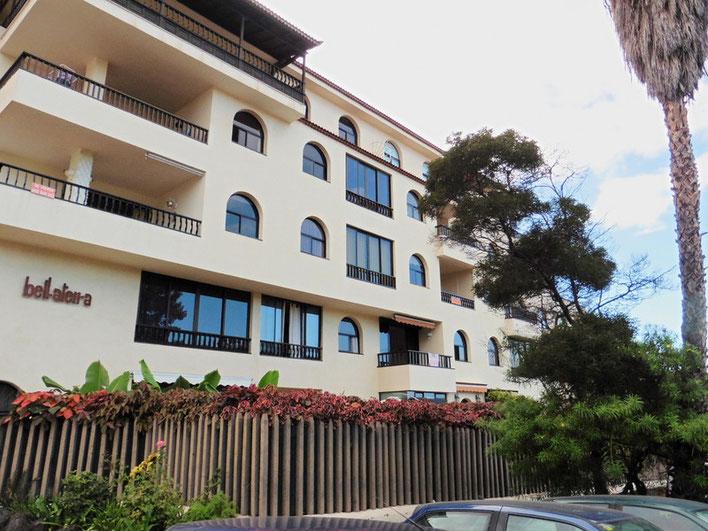 Helles freundliches Wohnhaus mit 5 Etagen vor dem sich eine üppig bepflanzte Grünanlage befindet.