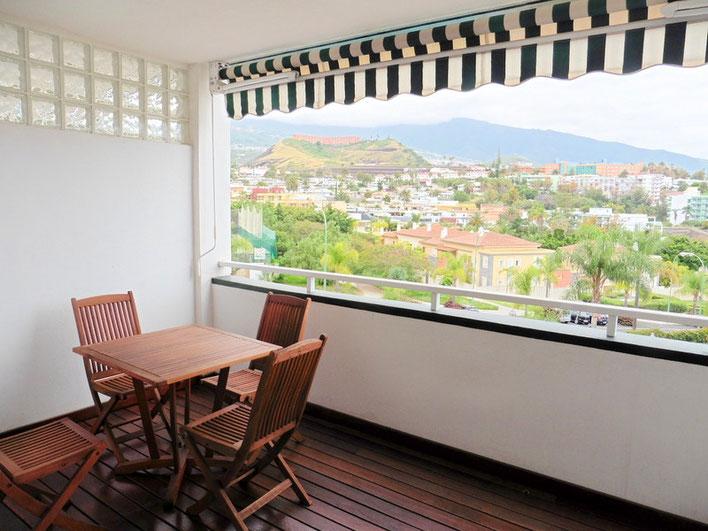 Ausblick vom Balkon mit Holzmöbel auf das Umland der Wohnanlage