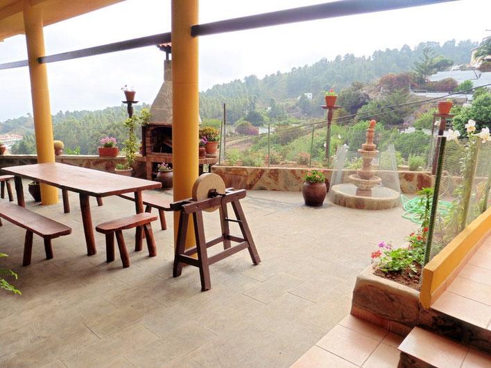 Große Terrasse mit Grill, rustikaler Bestuhlung und einem Weitblick über die Gipfel der Pinien bis zum Meer.