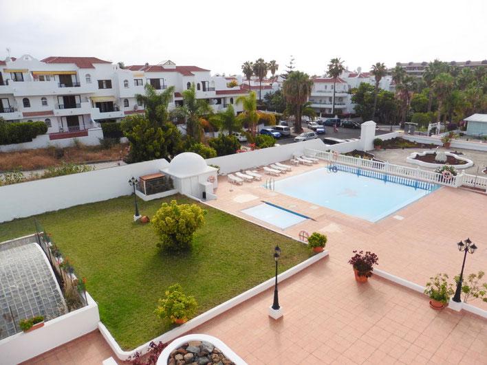 Ausblick vom Balkon zum Gemeinschaftsgarten mit Pool und im Hintergrund sieht man das Umland von La Paz.
