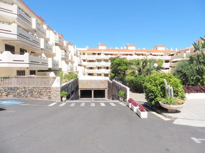 Einfahrt zur Tiefgarage unter der Wohnanlage mit subtropischer Bepflanzung auf der rechten Seite und links sind die Wohnungen.