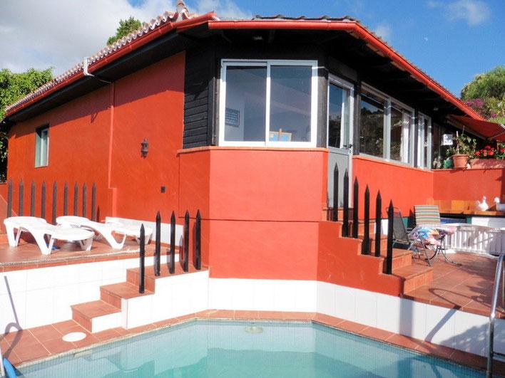 Blick auf das 2 Familienhaus, welches in Bordeauxrot gestrichen ist, vom Pool.