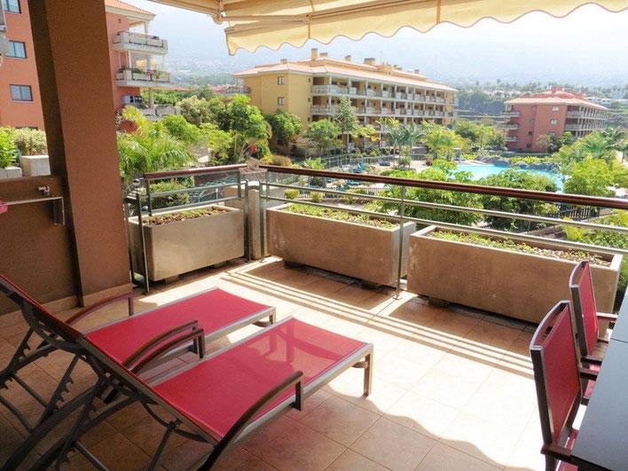 Vom Balkon sieht man direkt auf die Poollandschaft von der Wohnanlage und im Hintergrund sind die Berge zu sehen.