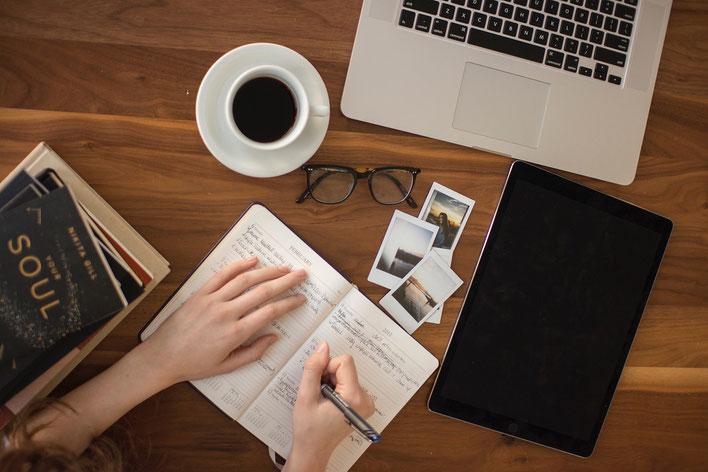 Notzubuch, schreibende Hände, Brille, Laptop