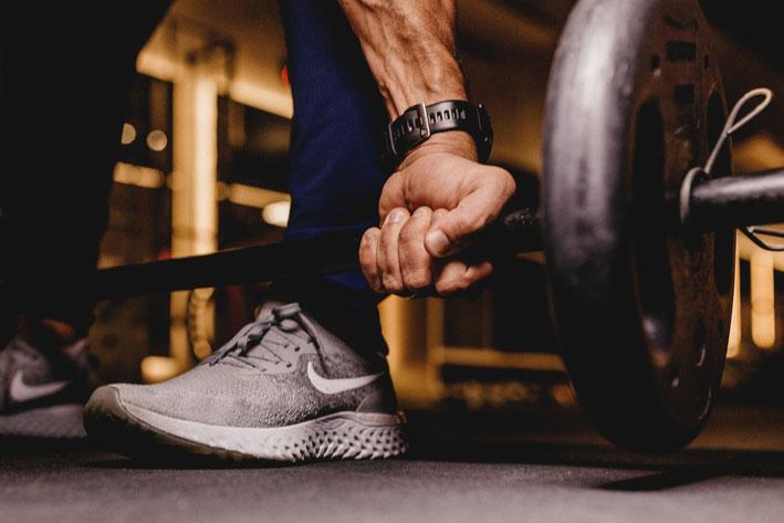 Ein Mann ist im Fitnessraum und macht Kreuzheben. Man sieht seine Hand, die die Langhantelstange greift. Die Stange befindet sich kurz über seinem Fuß.