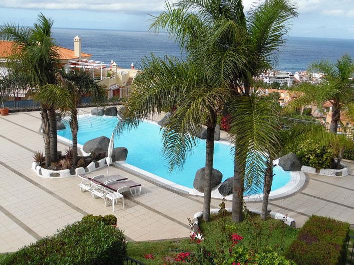 Blick auf den Pool, der mit Natursteinen und Palmen gestaltet ist, von der Wohnung aus. Im Hintergrund sieht man den Atlantik.