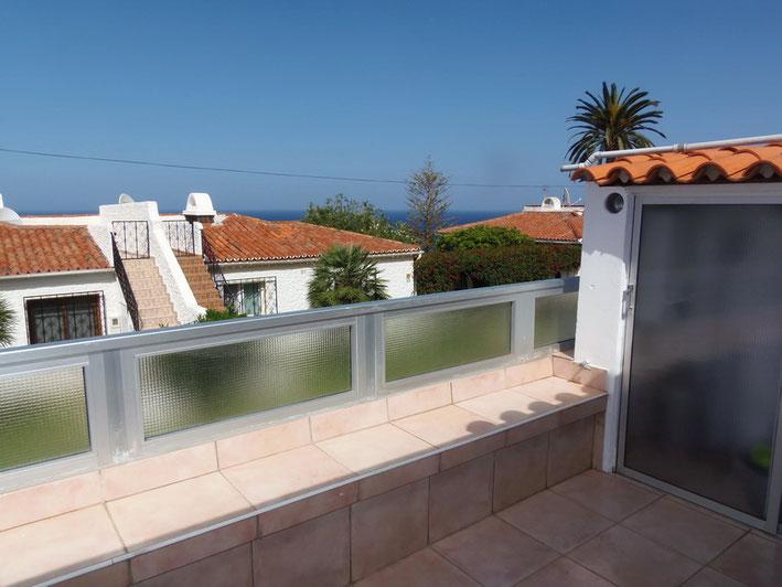 Blick auf die Chalets in der Nachbarschaft vom Balkon der Wohnung und im Hintergrund sieht man sogar das Meer.