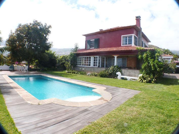 Mit Holz eingefasster Pool dann kommt eine grüne Rasenfläche und die Villa in Terrakotta Rot